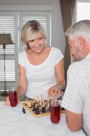 家でチェスを再生しながらドリンクと幸せな熟年カップル
