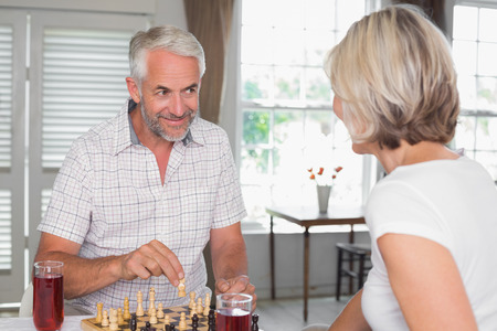 Happy mature couple with drinks while playing chess at home Фото со стока