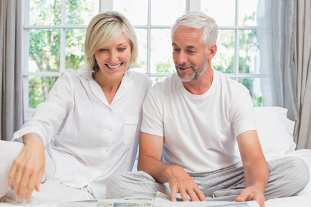 Portrait of a smiling mature couple sitting on bed at home Фото со стока