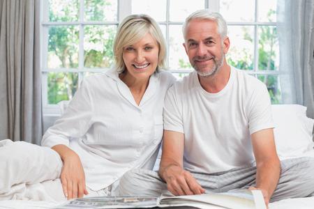 座っていると、自宅のベッドで新聞を読んで幸せな大人のカップル 写真素材