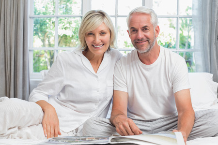 Happy mature couple sitting and reading newspaper on bed at home photo