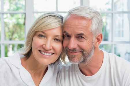 Close-up portrait of a happy mature couple smiling at home