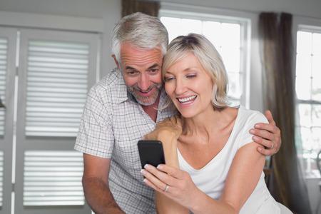 家庭でのテキスト メッセージを読んで元気な熟年カップル 写真素材