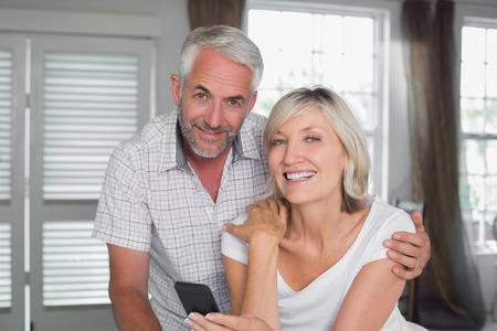 家庭でのテキスト メッセージを読んで幸せな熟年カップルの肖像画