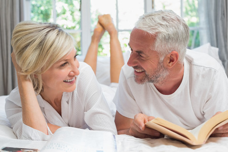 Happy mature couple lying and reading book in bed at home Фото со стока