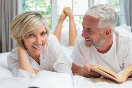 mature adult women: Happy mature couple lying and reading book in bed at home Stock Photo