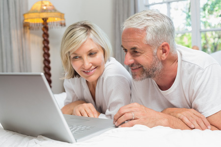 幸せな熟年カップルの横になっていると、自宅のベッドでノート パソコンを使用して 写真素材