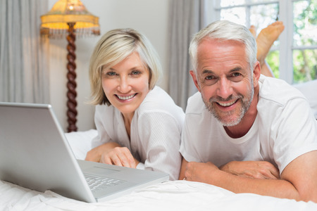 Portrait of a happy relaxed mature couple using laptop in bed at home photo