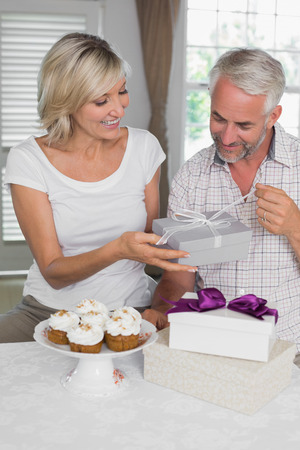 gifting: Happy woman giving a gift box to smiling mature man at home
