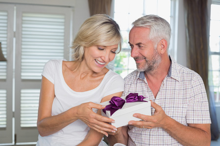 gifting: Portrait of a happy mature couple with a gift box at home