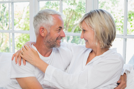 Loving happy mature couple with arm around sitting in bed at home photo