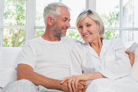 Portrait of a happy mature couple sitting in bed at home photo