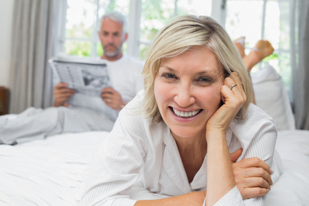 Close-up portrait of a smiling woman with man reading newspaper in background on bed at home photo