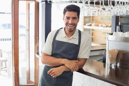 mesero: Retrato de un joven camarero sonriente confianza de pie en el mostrador de la cafeter�a