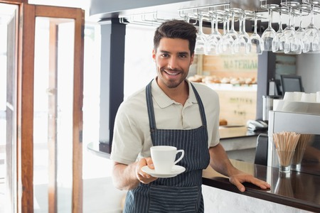 Young waiter smiling and holding cup of coffee at the café photo