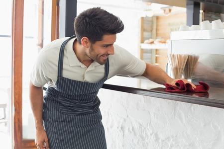 Junge lächelnde Kellner Reinigungsplatte mit Schwamm
