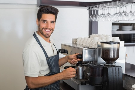 Side view portrait of a young waiter smiling and making cup of coffee at coffee shop Standard-Bild