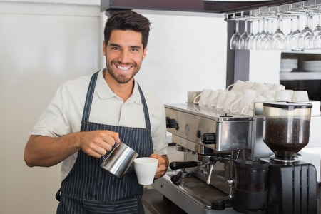 coffee machine: Portrait of a young waiter smiling and making cup of coffee at coffee shop