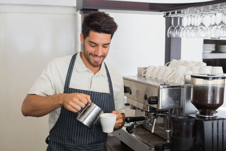 Portrait of a young waiter smiling and making cup of coffee at coffee shop photo