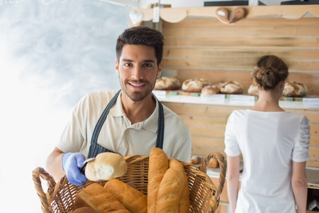Portrait of a happy confident young waiter with basket of breads at the coffee shop photo