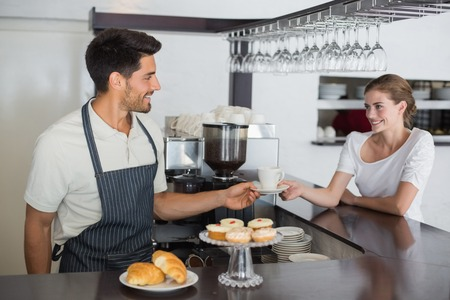 Portrait of a friendly waiter giving coffee to a woman at the coffee shop photo
