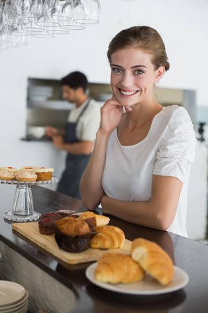 Portrait of confident female cafe owner with sweet food at counter photo