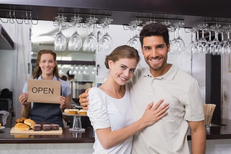 Portrait of a loving couple with female cafe owner at the coffee shop photo