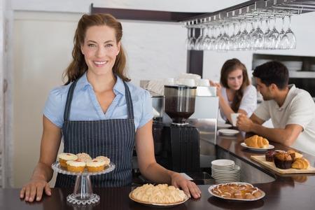 Portret van een glimlachende vrouwelijke cafe eigenaar met zoete hapjes en paar bij teller in de coffeeshop Stockfoto