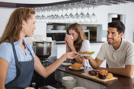 Friendly female cafe owner giving sandwich to a man at the coffee shop photo