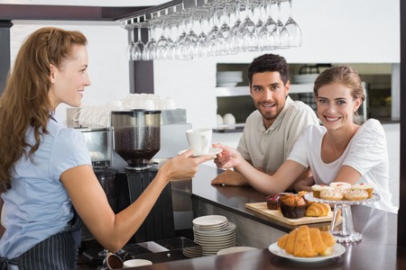Side view of a friendly female waiter giving coffee to a couple at the coffee shop photo