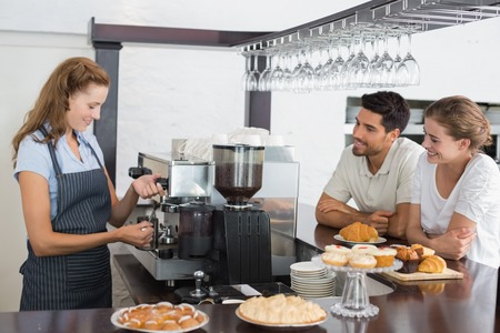 Side view of a smiling couple looking at waitress prepare coffee at the coffee shop Foto de archivo