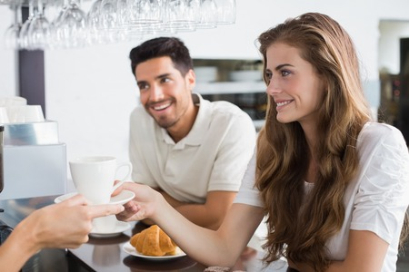 Close-up of a hand giving coffee to a couple at the coffee shop photo