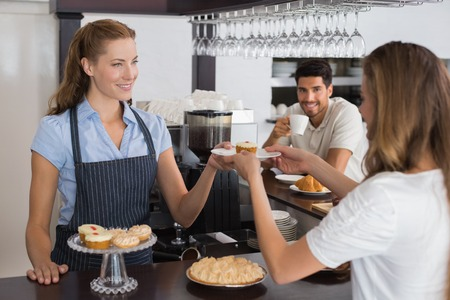 Friendly female cafe owner giving sweet food to a couple at the coffee shop photo