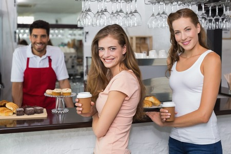 Portrait of a smiling male barista with women at counter in the coffee shop photo