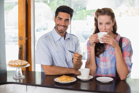 Portrait of a smiling young couple with man holding credit card at the coffee shop photo