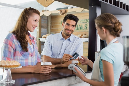 Side view of a couple paying bill at coffee shop using card bill photo