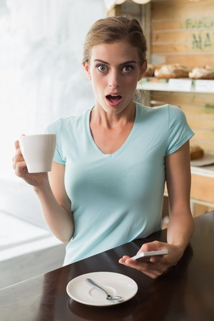 Shocked young woman with coffee cup reading text message at counter in the coffee shop photo
