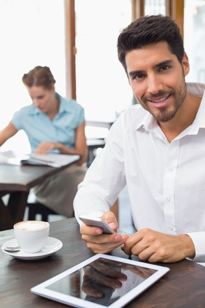 Portrait of a smiling young man text messaging in the coffee shop photo