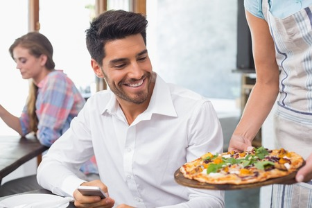 Waitress giving pizza to a smiling young man at the coffee shop photo