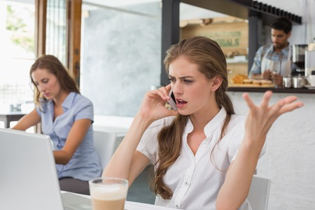 Annoyed young woman using mobile phone in the coffee shop Standard-Bild
