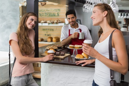 Portrait of female friends with male barista at counter in the coffee shop photo