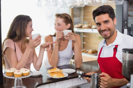 Smiling young women drinking coffee with male barista at counter in the coffee shop photo