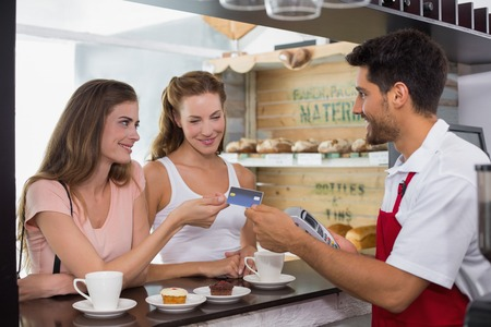 Smiling young friends with woman holding out credit card at the coffee shop photo
