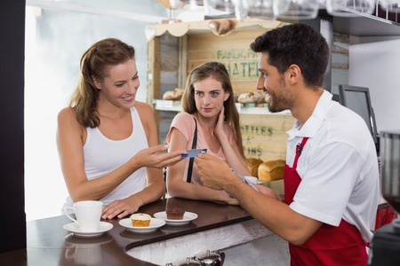 Side view of female friends paying bill at coffee shop using card bill photo