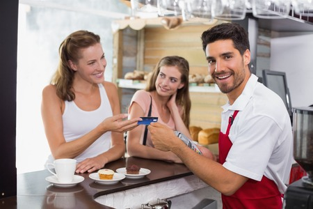 Smiling young female friends paying bill at coffee shop using card bill photo