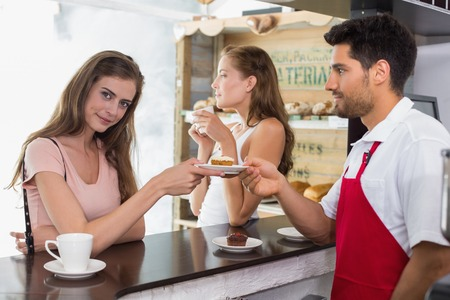Side view of a male barista giving pastry to woman at counter in the coffee shop photo