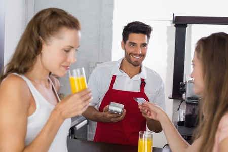 Young women paying bill while drinking orange juice at coffee shop using card bill photo