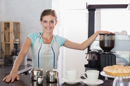 Portrait of a confident smiling female barista preparing standing at coffee shop