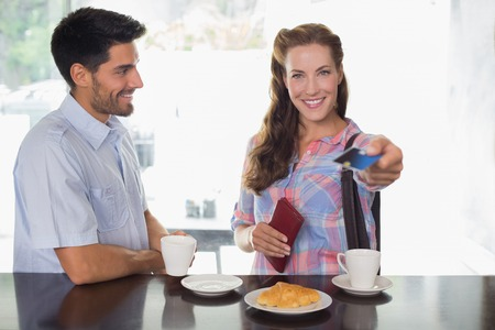Portrait of a smiling young couple with woman holding out credit card at the coffee shop photo