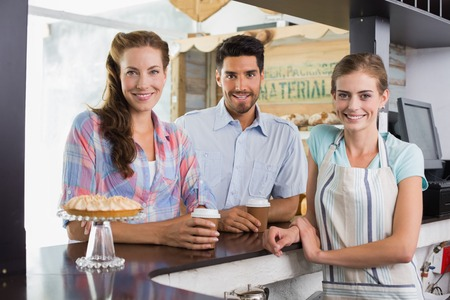 Portrait of a smiling female barista with a couple at counter in the coffee shop photo